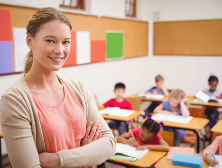 Pretty teacher smiling at camera at top of classroom