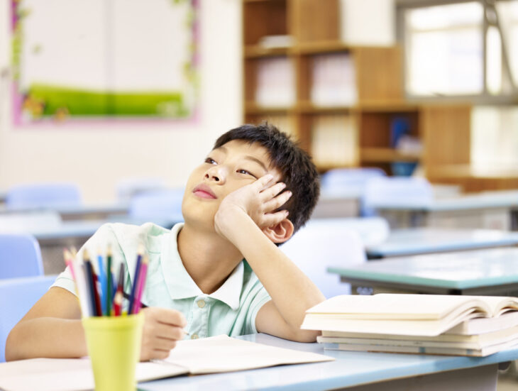 Asian pupil thinking in classroom